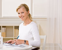 Woman writing checks Royalty Free Stock Photos