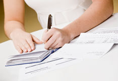Woman writing checks from checkbook Stock Photo