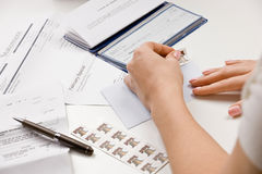Woman writing checks from checkbook. To pay monthly bills and stamping return envelope stock image