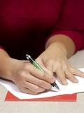 Woman writing Christmas card Royalty Free Stock Image