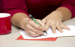 Woman writing Christmas card Royalty Free Stock Image