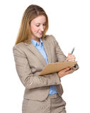 Woman writing on clip-board Royalty Free Stock Images