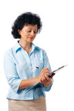Woman Writing with Clipboard. Portrait of a mature woman taking notes over white background Stock Image