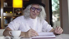 Woman is writing in diary. Woman is writing in journal, diary stock video footage