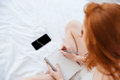 Woman writing in diary and listening to music from smartphone Royalty Free Stock Photography