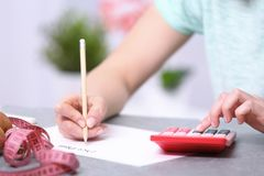 Woman writing a diet plan. And calculating calories Royalty Free Stock Images