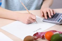 Woman writing a diet plan. And calculating calories Stock Photo