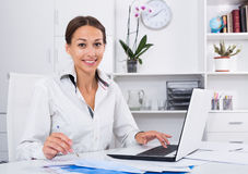 Woman writing down information. Cheerful woman writing down information from laptop at company office Stock Photo