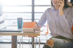Woman writing down informations. Cropped portrait of businesswoman talking on mobile writing down informations Royalty Free Stock Images