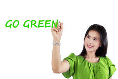 Woman writing Go Green. Beautiful Asian woman wearing green clothes and writes a text of Go Green on transparent screen. Concept of Earth Day royalty free stock image