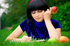 Woman writing in green field. Attractive young woman lying on green grass and writing in book with fresh, ripe apples Royalty Free Stock Image