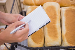 A woman writing a grocery list above bread loaf Royalty Free Stock Image