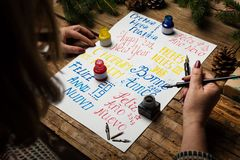 Woman writing happy new year in different languages. Woman writing happy new year in many different languages calligraphy stock photography