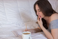 Woman writing in her notebook. Beautiful young woman lying on the bed and writing in her notebook while drinking a coffee Stock Photos