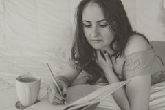 Woman writing in her notebook. Young woman lying on the bed and writing in her notebook Stock Photo