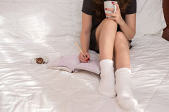 Woman writing in her notebook. Young woman lying on the bed, writing in her notebook and drinking coffee Royalty Free Stock Photography