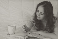 Woman writing in her notebook. Young woman lying on the bed, writing in her notebook and drinking coffee Stock Photo