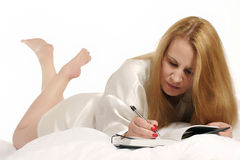 Woman writing in journal Stock Images