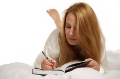Woman writing in journal Stock Photo