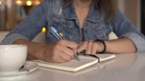 Woman writing in journal, diary. Close up stock footage