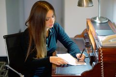 Woman writing a letter. A woman happy while writing a letter on her desk at home. Vertical shot. A girl is writing a letter to get out of work. The concept of stock images