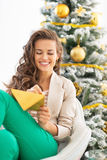 Woman writing letter near christmas tree Stock Photos