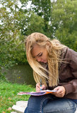 Woman writing letter in the park Stock Photography