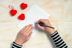 Woman writing love letter card for Valentines day Stock Photo