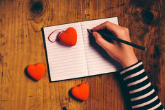 Woman writing love letter card for Valentines day Stock Images