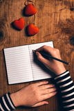 Woman writing love letter card for Valentines day Stock Image