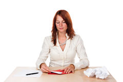 Woman writing love letter - low. Low angle shot of a woman that finishes her love letter with rejected versions on the right. On white background royalty free stock photo