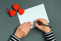 Woman writing love letter for Valentines day Stock Image