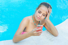 Woman writing a message in the pool Stock Photos