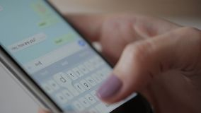 Woman is writing messages on her smartphone, close up. Young lady with beautiful manicure holding brand-new device her hand and typing greetings to her friend stock video footage