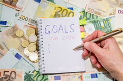Woman writing new years resolution list against euro banknote Stock Image