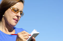 Woman writing a note. Attractive looking mature woman with a serious and concentrated expression on her face is writing a note in a book, with spotless blue sky Stock Images
