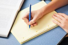 Woman writing in a note pad Stock Images