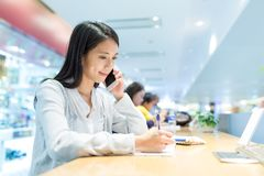 Woman writing on the note and talk to cellphone in coffee shop Royalty Free Stock Images