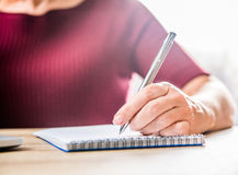 Woman writing in notebook. Close-up partial view of woman writing in notebook Royalty Free Stock Photography