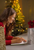Woman writing in notebook list of purchasings Royalty Free Stock Images