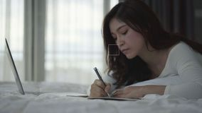 Woman writing notebook and using laptop computer on bed stock video