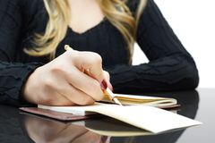 Woman is writing in notepad Stock Photo
