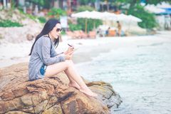 Woman writing on notepad with a pen at the beach. Stock Photography