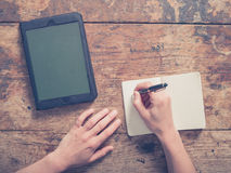 Woman writing in notepad and using tablet Stock Image