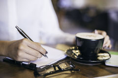 Woman writing notes in her a cafe Stock Photo