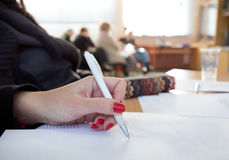 Woman writing notes on lecture Stock Photos