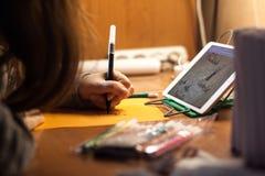 Woman Writing on Orange Paper Stock Image