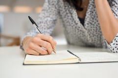 Woman writing on organizer Royalty Free Stock Photos