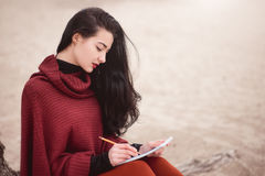 Woman writing outdoors Royalty Free Stock Image