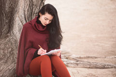 Woman writing outdoors Stock Image